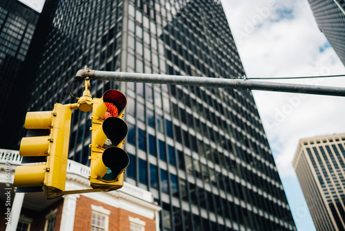 Equipment for controlling transport on ras hanging on urban background in modern business district of megalopolis, yellow traffic lights warning cars and pedestrians on intersection in downtown.