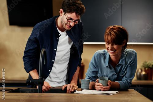 Fototapeta Couple laughing in their kitchen obraz na płótnie