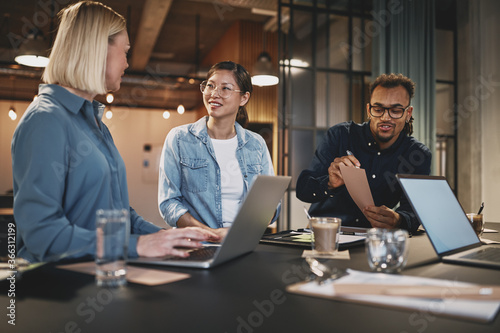 Diverse businesspeople smiling while working around an office table - 366312199
