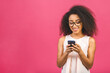 Leinwandbild Motiv Happy young african american woman casually dressed standing isolated over pink background, holding mobile phone.