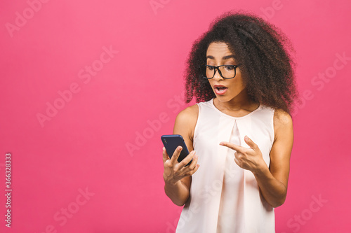 Fototapeta Attractive curly dark skinned american female with Afro hairstyle looks agitated at screen of smart phone, impressed by message content recieved from friend, has surprised facial expression