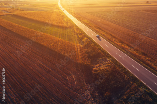 Obraz Cars driving down the road through countryside in autumn - fototapety do salonu