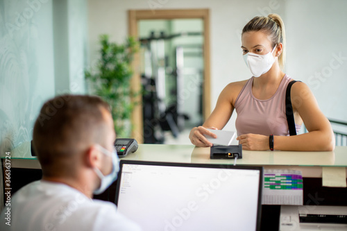 Fotografering Athletic woman with face mask using smart phone while checking in at the gym