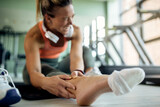 Close-up of female athlete feeling pain in her ankle during sports training at health club.