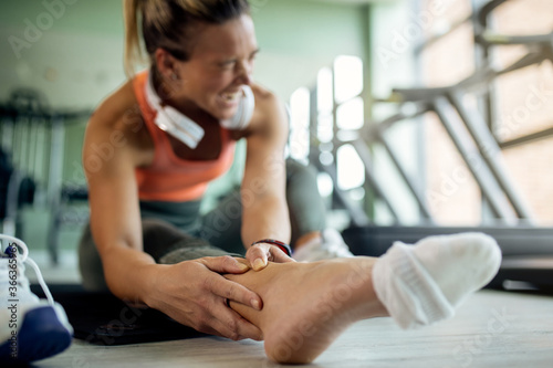 Photo Close-up of female athlete feeling pain in her ankle during sports training at health club
