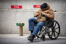 A Disabled Homeless Veteran Sits In A Wheelchair On A Sidewalk In New York City.