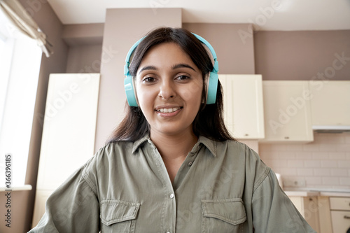 Photo Indian teen girl college student teacher wearing headphones looking at web cam distance learn or teach online