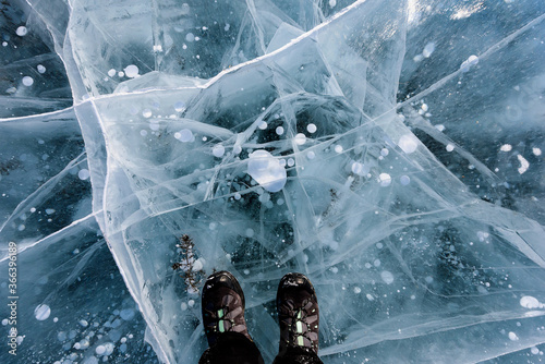 Beautiful ice of Lake Baikal with abstract cracks with shoes. Top view