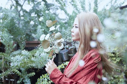 光と植物と赤い服を着た女性のフォトジェニックなイメージ写真