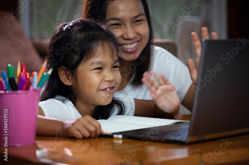Fotografiet Asian child girl using notebook to learning online technology with her mother to advise beside