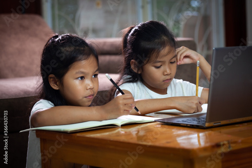 Obraz na plátne Two asian child girls using notebook to learning online technology with her sister together