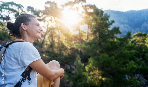 Fotografie, Obraz Young beautiful girl enjoying the forest and nature at sunset, walking in the wo