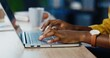 canvas print picture - Close up shot of African American female hands typing on laptop while sitting at office desk indoors. Woman fingers tapping and texting on computer keyboard while working in cabinet. Work concept