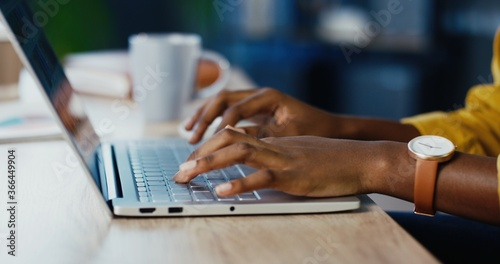 Stampa su Tela Close up shot of African American female hands typing on laptop while sitting at office desk indoors