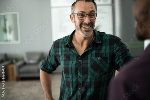 Slika na platnu Mature businesswoman laughing while talking with an office colleugue