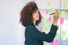 African American Businesswoman Writing On Sticker With Marker. Focused Confident Curly Female Manager Sharing Idea For Project And Making Note. Brainstorming, Business And Management Concept