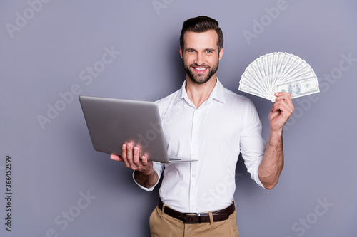 Portrait of his he nice attractive rich successful cheerful brunet guy using laptop holding in hands investment playing online casino game bet isolated over gray pastel color background