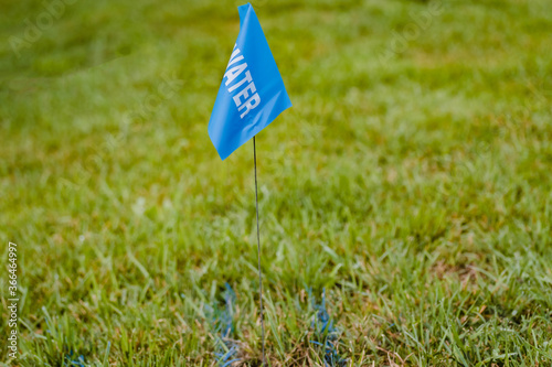 Fotografija a blue surveyors flag and stake marks the location of a water pipe