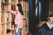 Young Woman In Casual Outfit Standing Near Shelves Choosing Book For Read Enjoying Literature On Free Time, Intelligent Female Student Choosing Text Book For Learning Spending Time In Library.