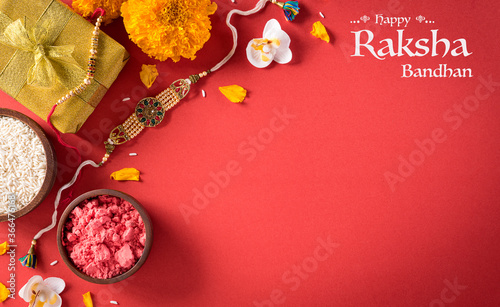 Raksha Bandhan, Indian festival with beautiful Rakhi and  Rice Grains on red background.  A traditional Indian wrist band which is a symbol of love between Sisters and Brothers.