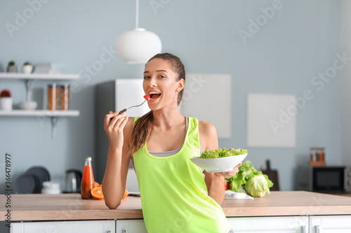 Fotografia Beautiful young woman eating vegetable salad in kitchen