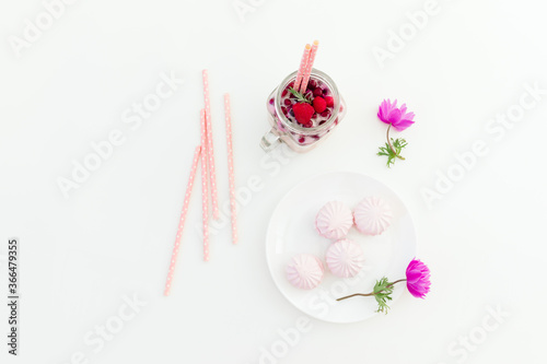 Berries smoothie with straws, marshmallow and anemones flowers on white backgrou Canvas Print