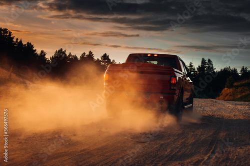 Pickup truck car in motion at country road with clouds of dust Canvas Print