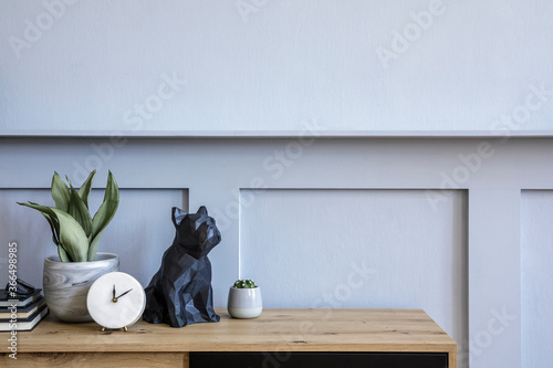 Stylish scandinavian composition with wooden commode, candle, succulent in pot, books, white clock, decoration, copy space and gray wood paneling in modern concept.