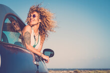 Attractive Curly Blonde Young Woman Smile And Enjoy The Wind Outside The Car - Concept Of Beauty And Travel For Happy And Cheerful Caucasian People - Alternative Lifestyle Female Feel The Freedom Joy