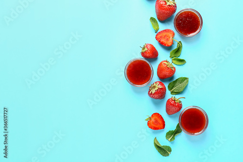 Bowls of tasty strawberry jam on color background