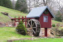 A Small Replica Red And Blue Old Mill Shed Building With Wooded Water Wheel And Stone Foundation