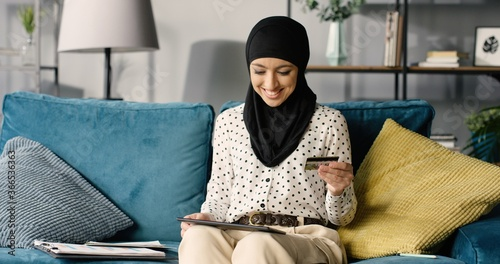Portrait of a young happy muslim woman in hijab at home using digital tablet shopping online with credit card while sitting on sofa Wallpaper Mural