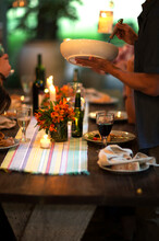 Person Standing At A Table Holding A Bowl, Wine Glasses, Plates, Flowers And Candles On The Table.