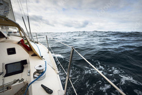 Fototapeta White yacht sailing in the North sea on a cloudy day. Dark storm sky reflecting in the water. Rogaland region, Norway. Sport, recreation, leisure activity theme obraz