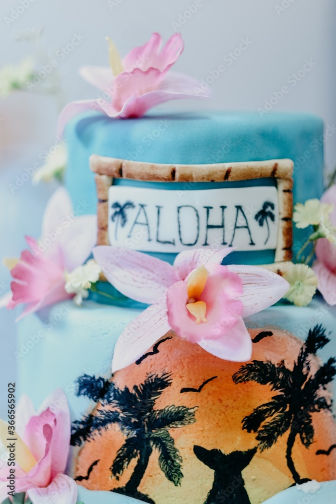 Vertical shot of a Hawaiian thematic cake decorated with pink flowers and 'aloha' text