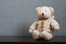 Cute Teddy Bear Sitting On Wooden Table Wearing A Warm Buttoned Duffel Coat With Hood And Pocket Isolated On Dark Gray Background. Empty Space For Text