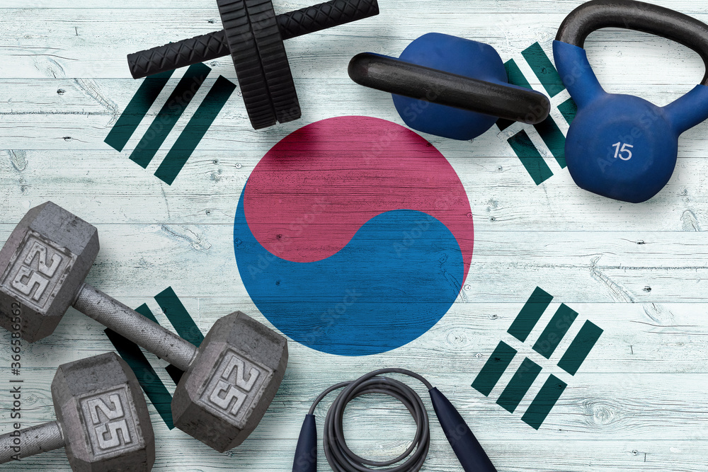 Fototapeta South Korea sports club concept. Top view of heavy weight plates with iron bar on national background.