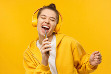Young Girl In Yellow Hoodie And Wireless Headphones, Singing With Closed Eyes, Holding Tphone As Microphone, Isolated On Studio Background