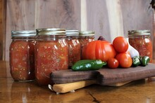 Fresh Tomatoes And Jalapenos From A Family Farm Vegetable Garden With Garlic And Red Onion For Home Canned Spicy Salsa In Glass Jars On A Rustic Background