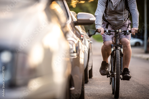 Obraz An unidentified man riding a bicycle passing cars on the road in the traffic. A cyclist overtaking cars with high speed. - fototapety do salonu
