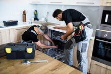 Repair Company For You. Aged Repairman In Uniform Fixing Dishwasher In The Kitchen, While His Young Colleague Helping Him, Holding Flashlight. Repair Service Concept