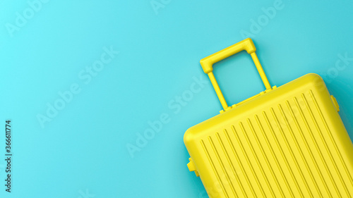 Fotografia Yellow luggage baggage on blue background, minimalist creative mockup, top view
