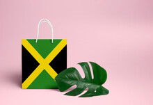 Jamaica Shopping Concept. National Cardboard Shopping Bag With Monstera Leaf And Pink Background. Online Shopping Theme.