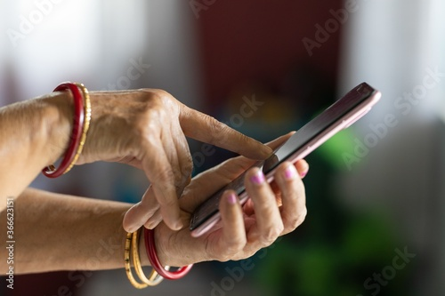 Female with wrinkled hands using a smartphone with a blurry background Fototapet