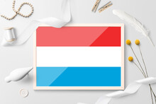 Luxembourg Flag In Wooden Frame On White Creative Background. White Theme, Feather, Daisy, Button, Ribbon Objects.