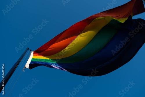 Photo bandera lgbt flameando en mástil con viento de fondo cielo despejado