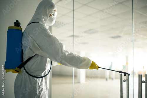 Fotografía Sanitary worker sprays an empty business center with antiseptical liquid to prevent covid-19 spread