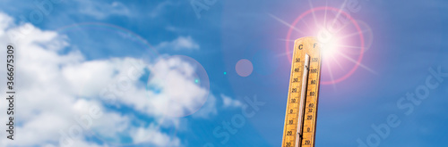 Foto Thermometer against blue sunny sky. Hot summer weather concept.