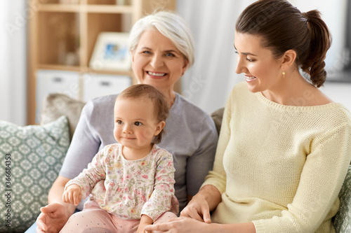 Fototapeta family, generation and female concept - happy smiling mother, baby daughter and grandmother sitting on sofa at home obraz