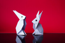 Simple Flat Lay Out. Two White Rabbits Paper Origami On Clear Background With Copy Space Concept